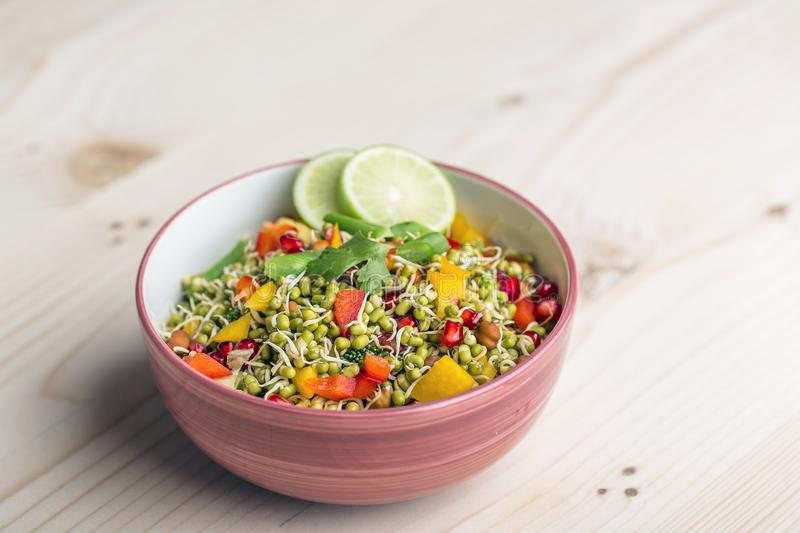 Sprouted lentil salad with sliced lemon. Sprouted salad with sliced lemon served in a bowl for good health stock image