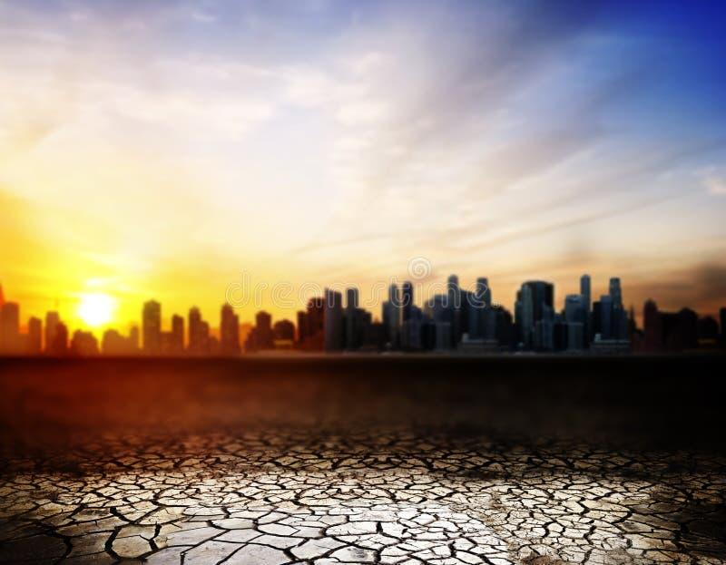 Sprucken ökenyttersida över solnedgång i stad arkivfoto