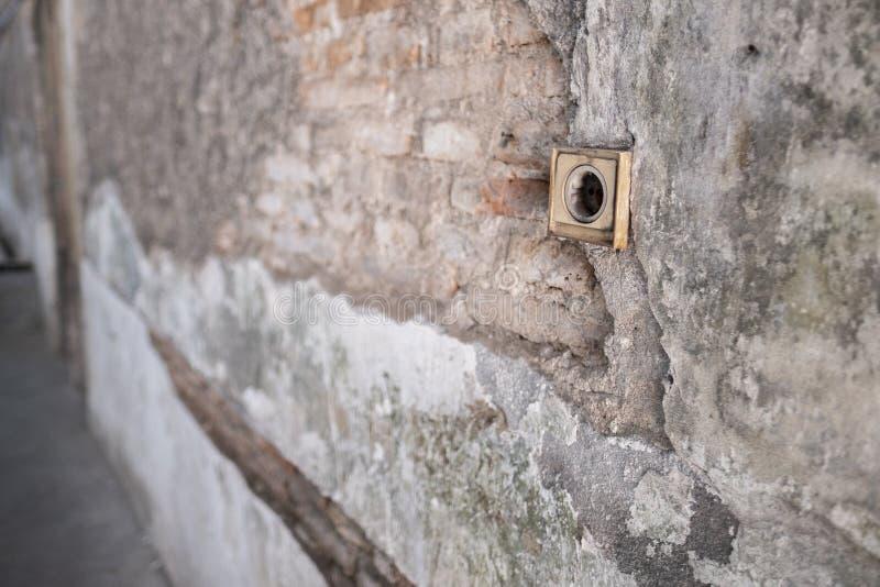 Sprucken konkret tappningvägg med elektriska Soket som förgrunden royaltyfri bild