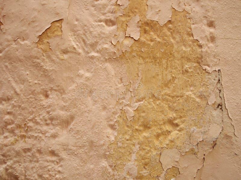 Sprucken skalande målarfärgtextur i skuggor av beige och gult på en gammal texturerad betongvägg royaltyfria bilder