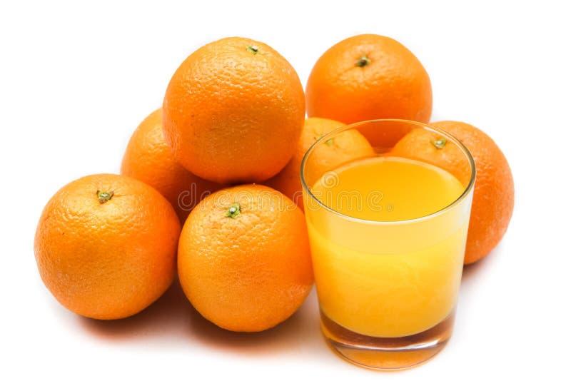 Sprudelnder Orangensaft von der schäumenden Tablette mit Orangen am Hintergrund stockbild