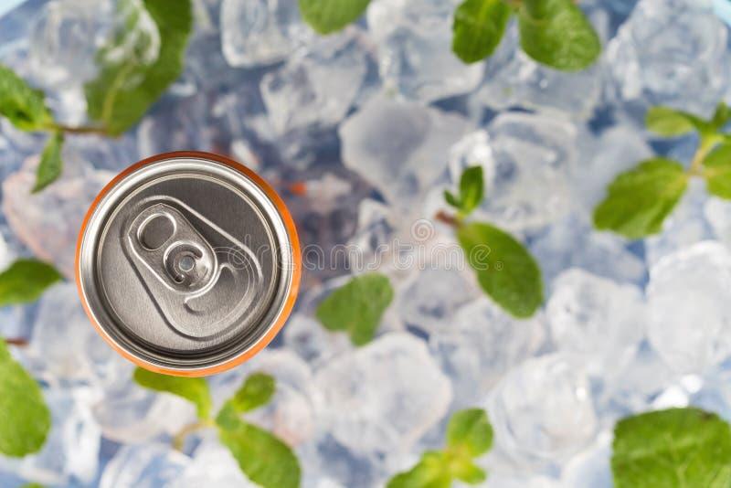 Sprudelndes Getränk in einer Aluminiumblechdose auf dem Hintergrund von Eiswürfeln und von frischen tadellosen Blättern Beschneid stockfoto
