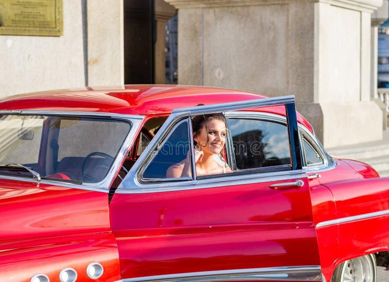spruit van de bruid de redactiefoto in een mooie rode uitstekende oude tijdopnemerauto van de jaren '60 in een stadscentrum stock afbeelding