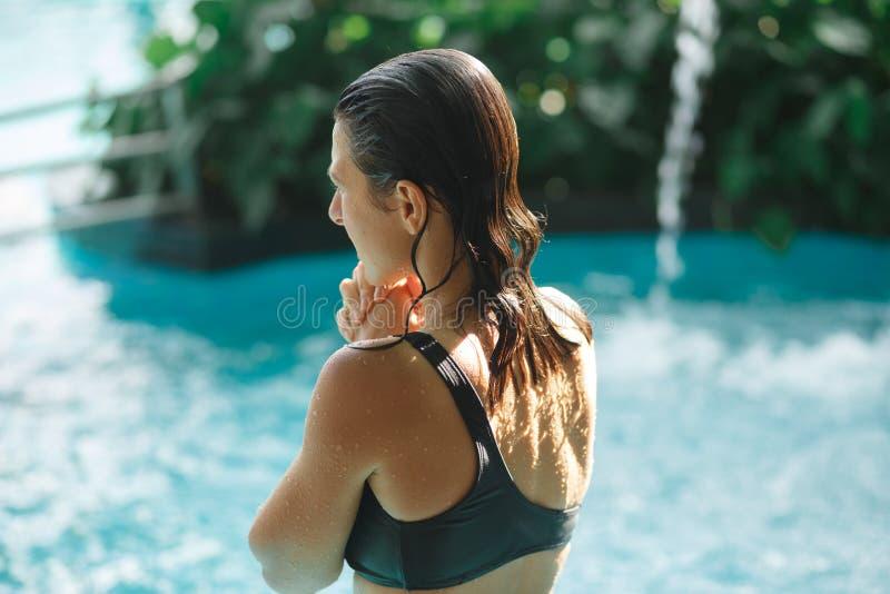 Spruit van rug van sexy slank wijfje in zwembad tussen groene struiken royalty-vrije stock foto's