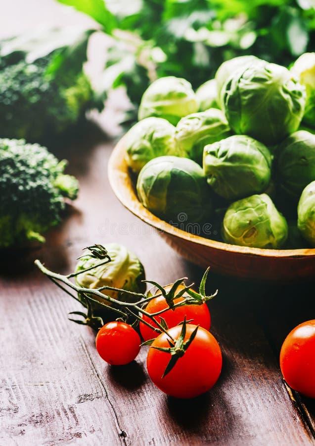 Spruitje, kersentomaat, broccoli, peterselie en greens op rustieke houten lijst royalty-vrije stock afbeeldingen