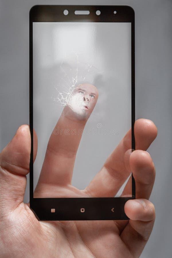 Sprung auf dem Glas vom über-Klopfen des Schirmes durch den Benutzer das menschliche Gesicht wird gegen das Glas des Telefons ged stockfotos