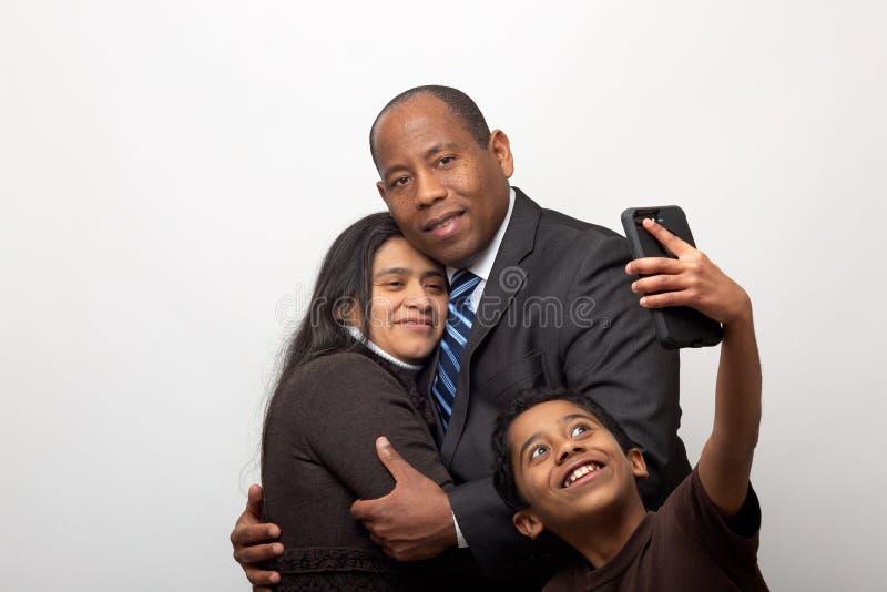 Sprungit blandat kopplar ihop att posera för fotoet och sonen som tar Selfie med den smarta telefonen arkivfoton