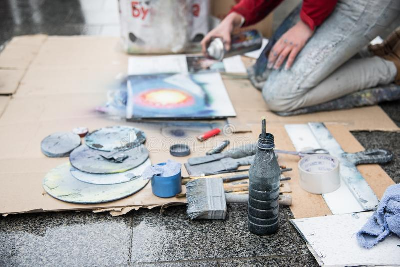 Sprutmålningsfärgshow för åhörare i mitt av gatan, uppsättning av funktionsdugliga hjälpmedel, workflow i bakgrunden, konst royaltyfri foto