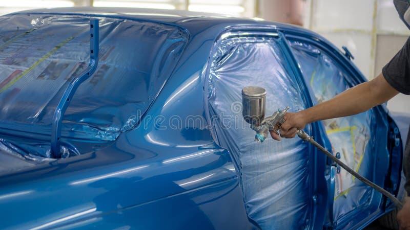 Sprutpistol med målarfärg för att måla en bil royaltyfri bild