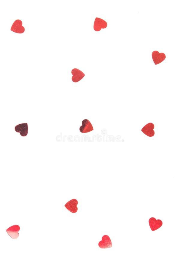 Spruzza i coriandoli sotto forma di cuore su un fondo bianco immagine stock libera da diritti