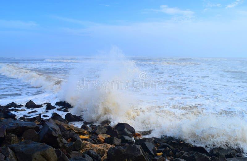 Spruzzamento di acqua con impatto dell'onda del mare sulle rocce a terra con cielo blu - sfondo acquatico naturale dell'Oceano immagini stock libere da diritti