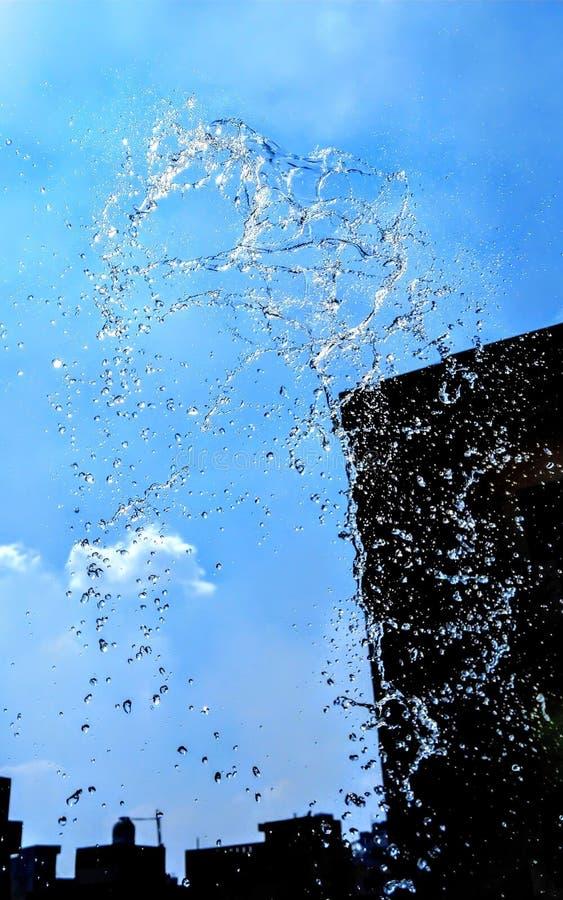 Spruzzando acqua isolata sul fondo blu fotografia stock libera da diritti