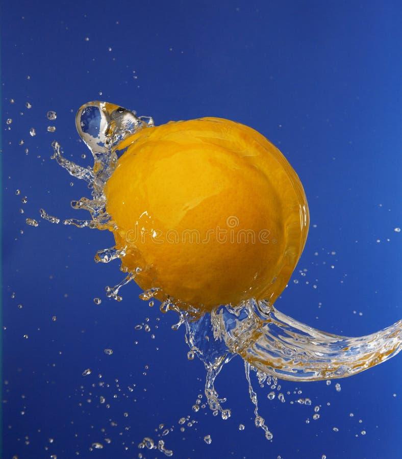 Spruzzata in acqua con un arancio immagini stock libere da diritti