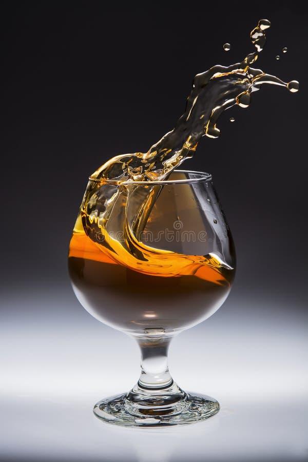 Spruzzata ambrata della bevanda dell'alcool in vetro fotografia stock