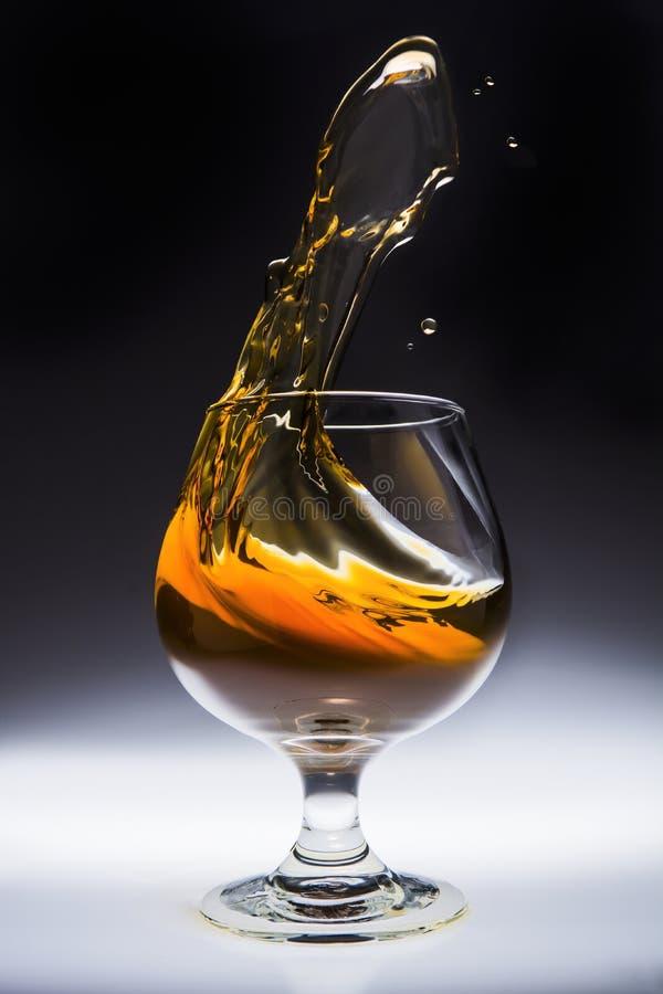 Spruzzata ambrata della bevanda dell'alcool in vetro immagini stock