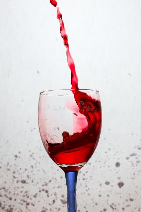 Spruzzata curva potente di vino rosso in un vetro con una gamba colorata fotografia stock libera da diritti