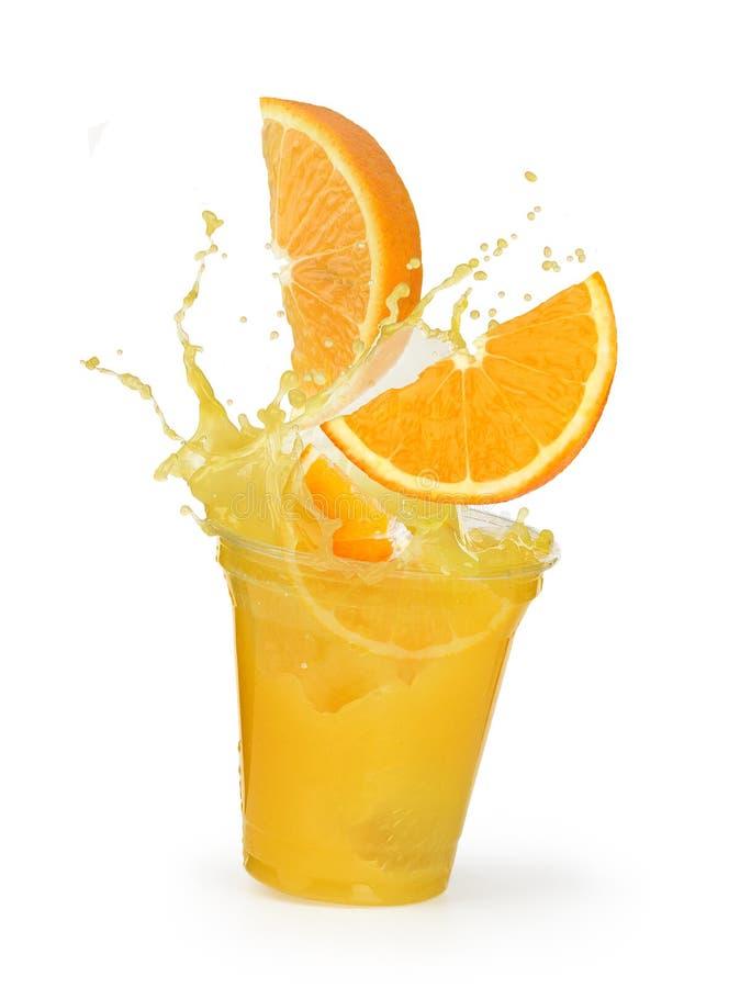 Spruzzata del succo d'arancia con le arance in una tazza di plastica fotografie stock libere da diritti
