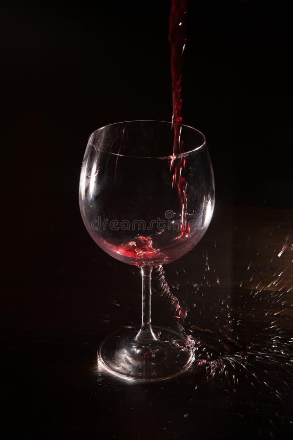 Spruzzata del vino rosso nel moto su fondo nero immagini stock