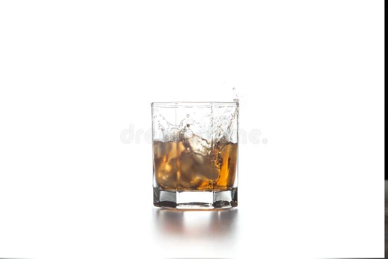 Spruzzata del whiskey dal cubetto di ghiaccio caduto in vetro con la bevanda su fondo leggero immagine stock