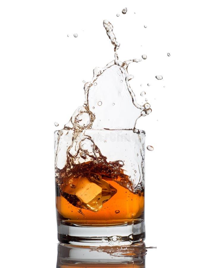 Spruzzata del whiskey isolata su un bianco fotografie stock libere da diritti