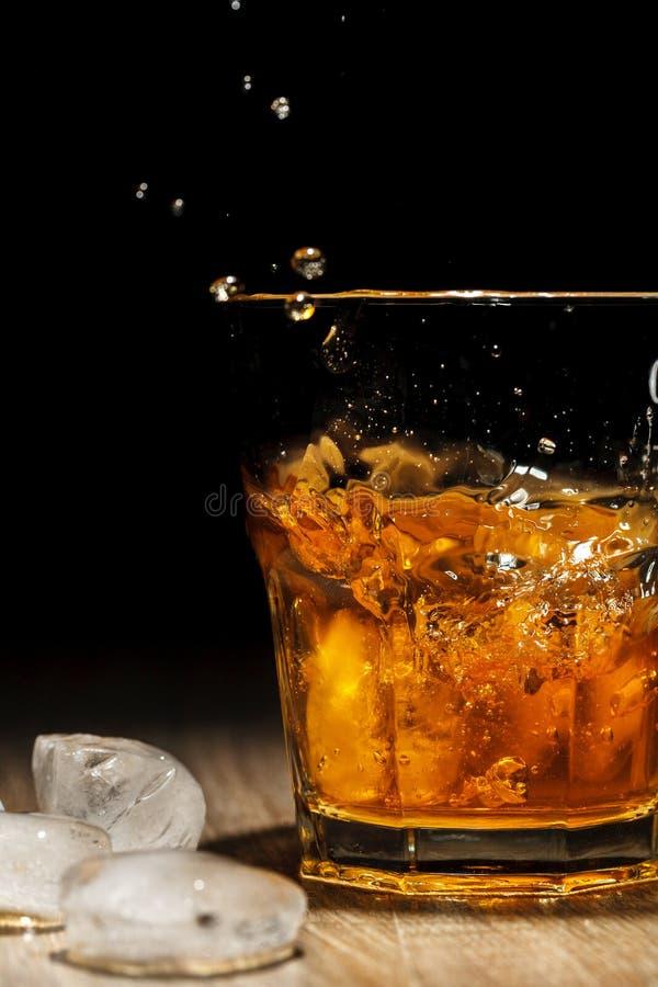 Spruzzata del whiskey in vetro su una tavola di legno fotografie stock