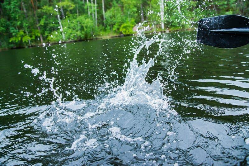 Spruzzata dell'acqua dalla pagaia di una barca fotografia stock