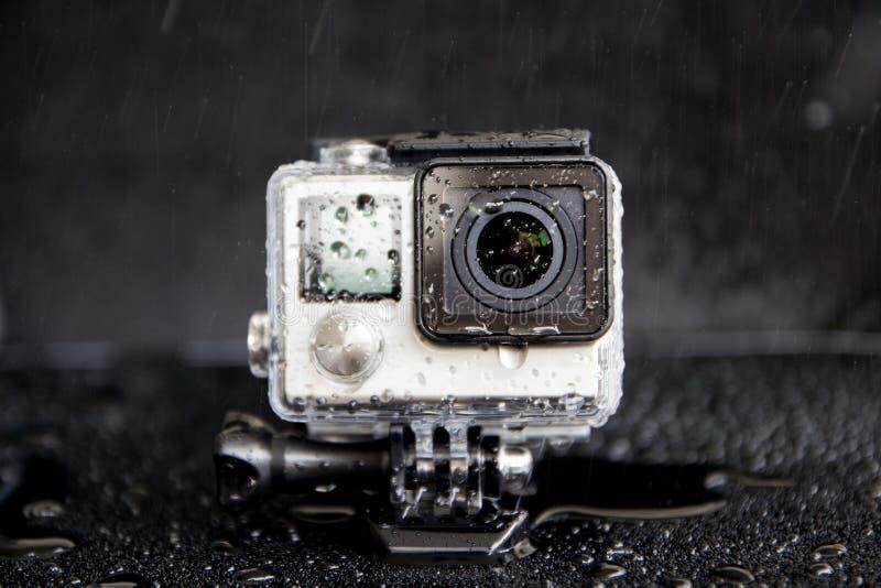 Spruzzata dell'acqua del primo piano sulla macchina fotografica estrema in impermeabile immagini stock