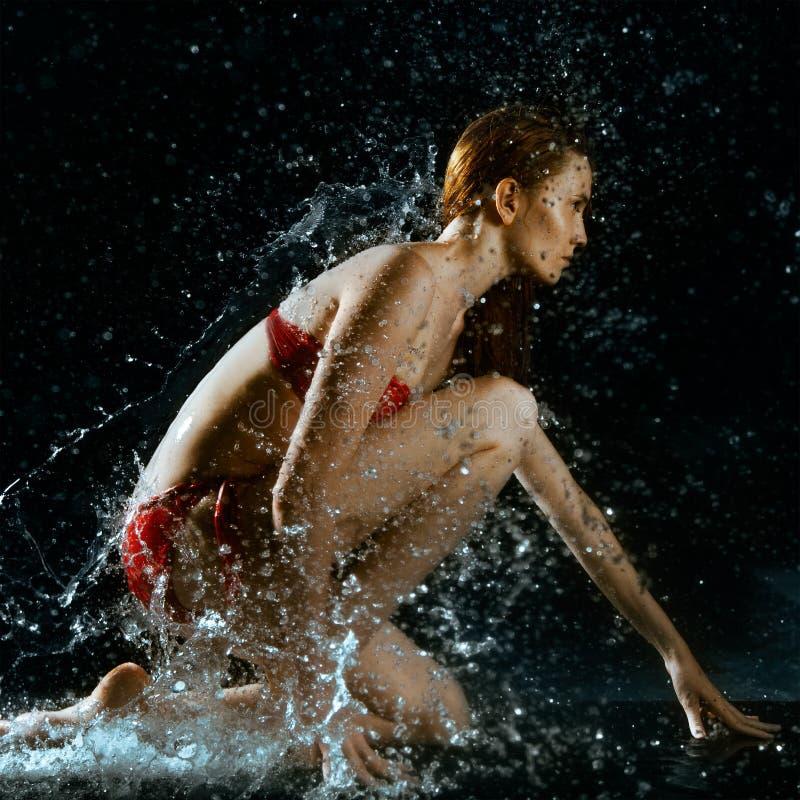 Spruzzata dell'acqua e della donna nello scuro fotografie stock libere da diritti