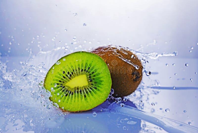 Spruzzata di acqua blu sulla fetta verde di kiwi immagini stock