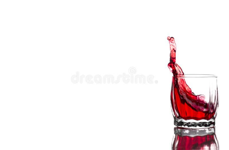 Spruzzata di succo rosso, vino in un vetro costolato di vetro del whiskey su un fondo bianco immagine stock libera da diritti