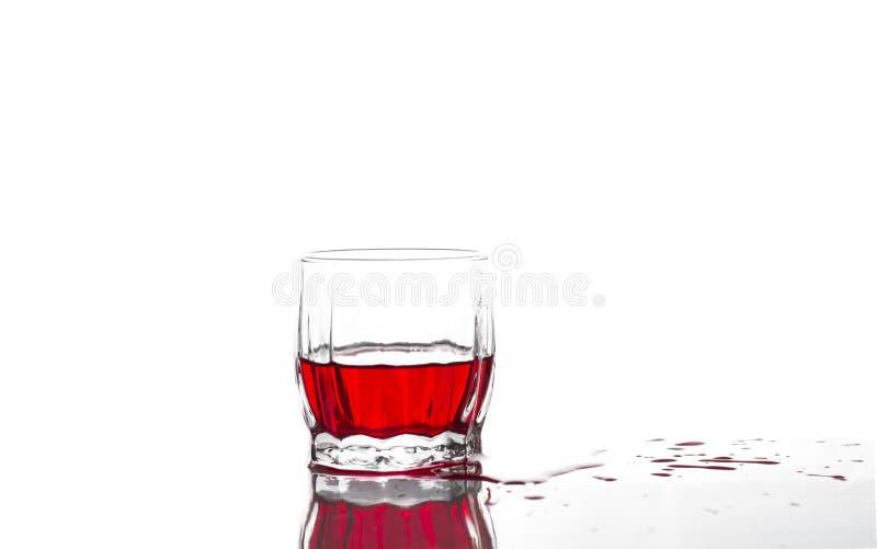 Spruzzata di succo rosso, vino in un vetro costolato di vetro del whiskey su un fondo bianco fotografie stock libere da diritti