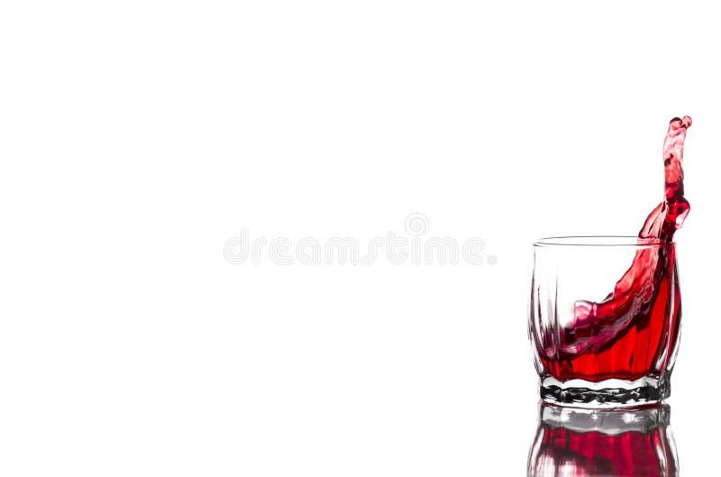 Spruzzata di succo rosso, vino in un vetro costolato di vetro del whiskey su un fondo bianco fotografie stock