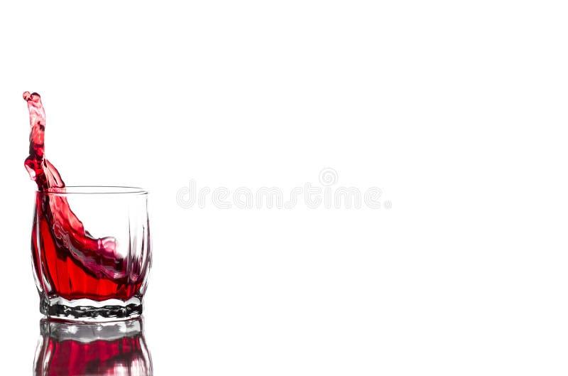 Spruzzata di succo rosso, vino in un vetro costolato di vetro del whiskey su un fondo bianco immagini stock