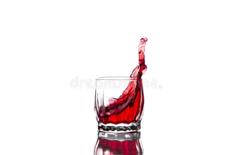 Spruzzata di succo rosso, vino in un vetro costolato di vetro del whiskey su un fondo bianco fotografia stock libera da diritti