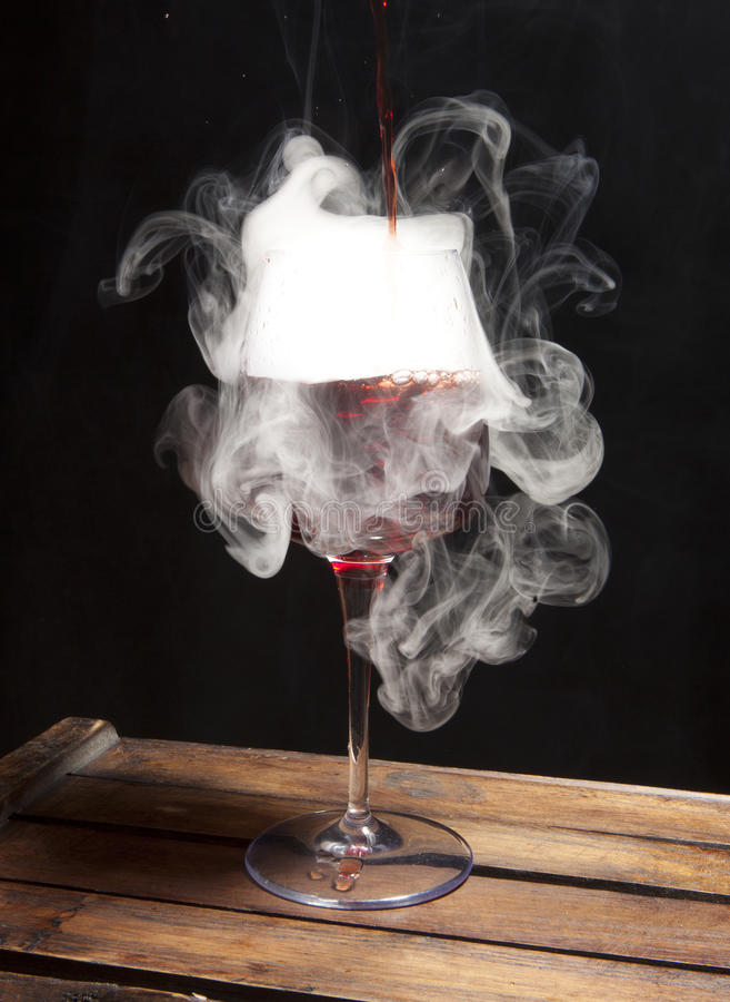 Spruzzata di vino nel vetro su backround scuro fotografia stock