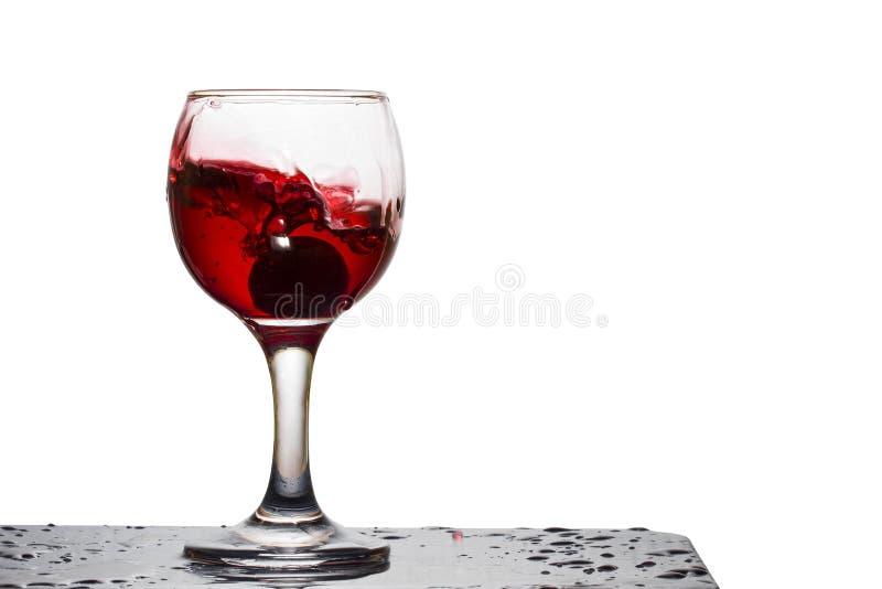 Spruzzata di vino rosso in un vetro con l'uva caduta immagini stock