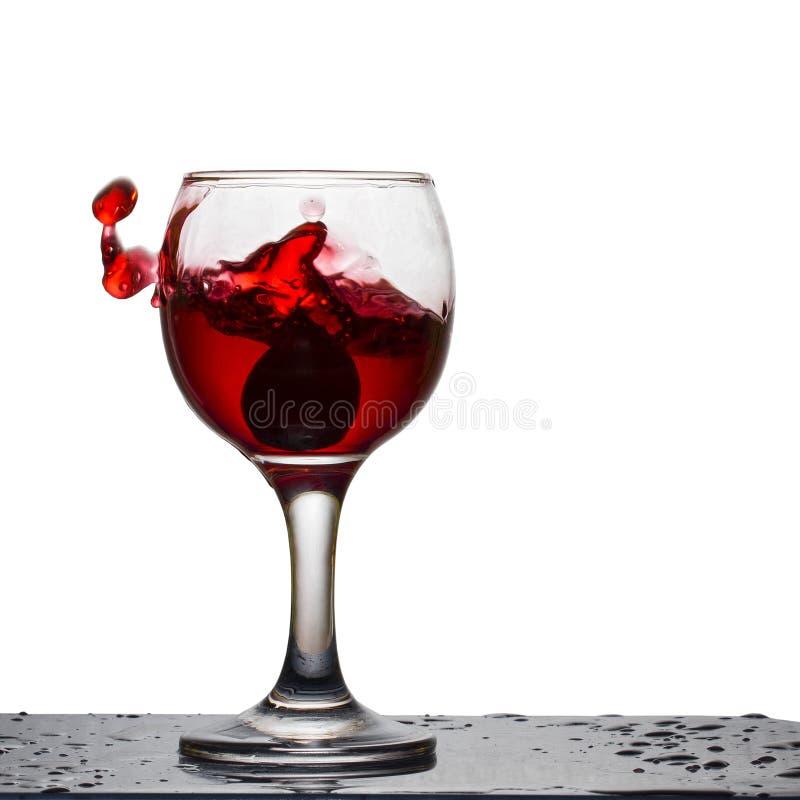 Spruzzata di vino rosso in un vetro con l'uva scura caduta immagine stock