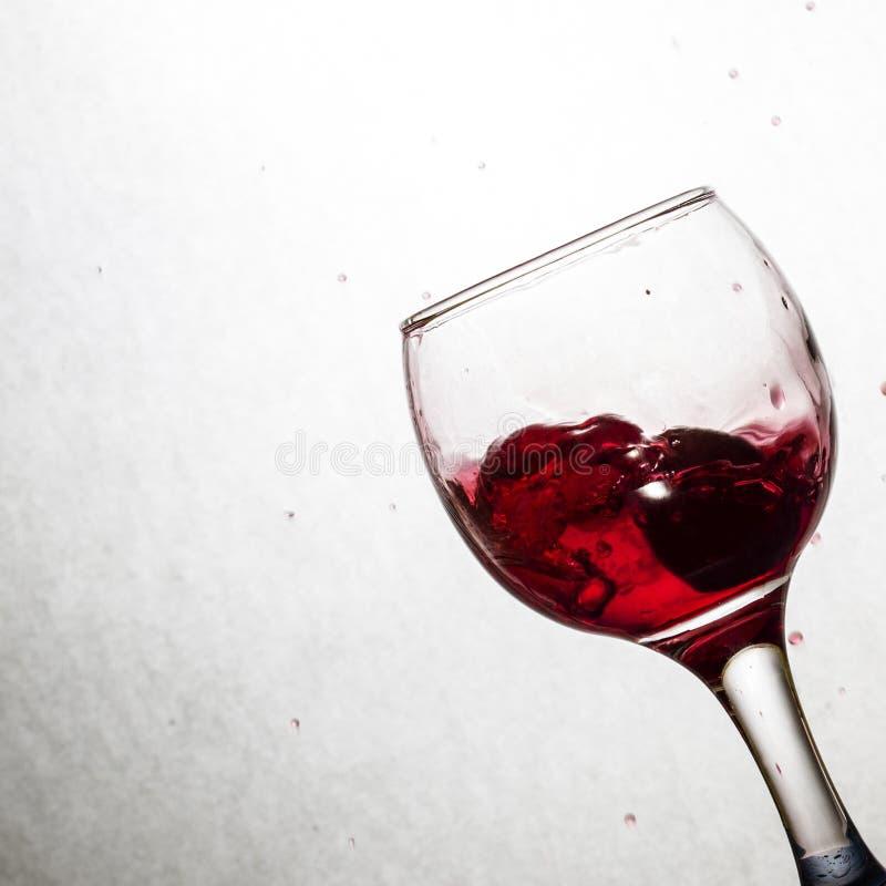 Spruzzata di vino rosso in un vetro inclinato fotografia stock libera da diritti