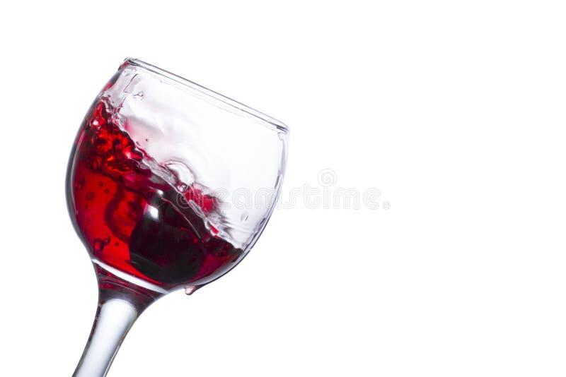 Spruzzata di vino rosso in un vetro inclinato con l'uva caduta fotografia stock libera da diritti
