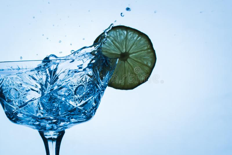 Spruzzata gloriosa di acqua in un vetro con una fetta di limone fotografie stock libere da diritti