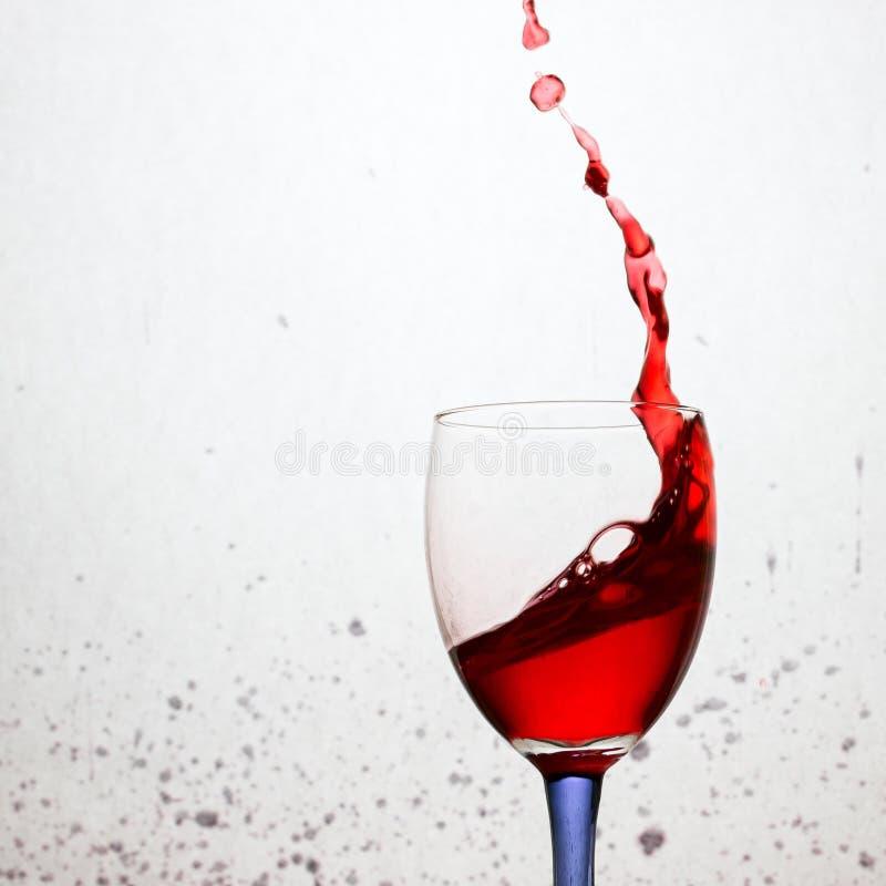 Spruzzata spettacolare della bevanda per un vino rosso amoroso in un vetro fotografia stock libera da diritti
