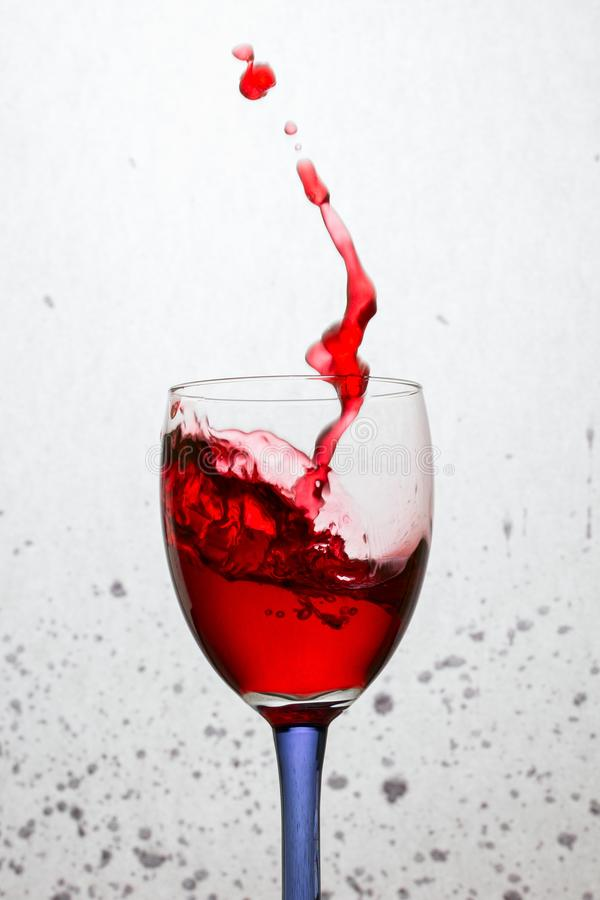 Spruzzata spettacolare di vino rosso in un vetro con un gambo colorato immagini stock
