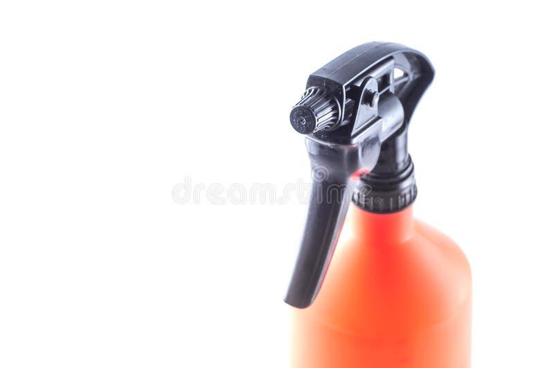 Spruzzatore del giardino per cura ed il giardinaggio del fiore Carro armato arancio luminoso e pompa di plastica nera Su un fondo immagine stock