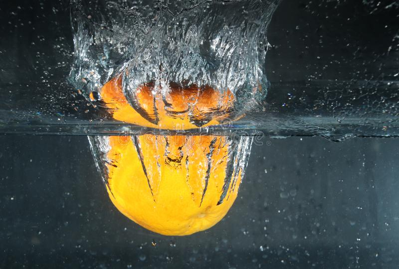 Spruzzatura arancio nell'acqua fotografia stock