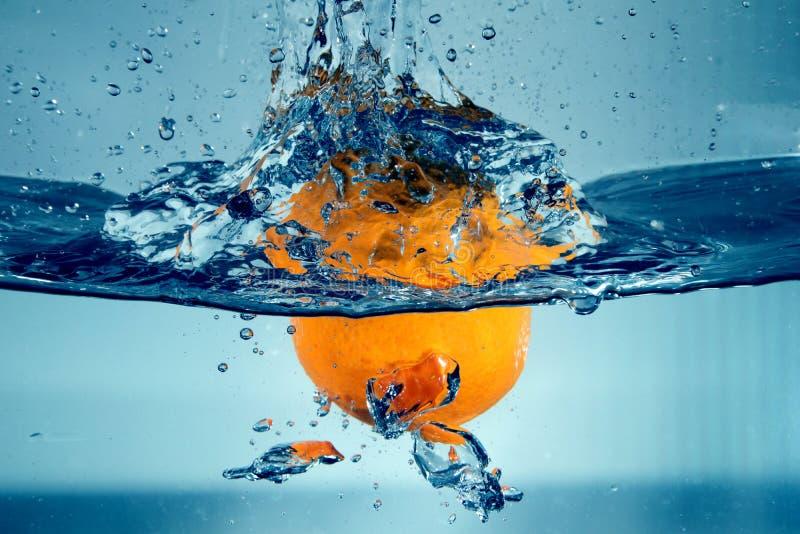 Spruzzatura arancio nell'acqua immagini stock libere da diritti