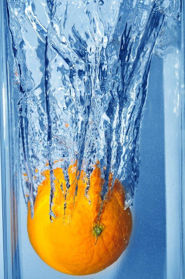Spruzzatura dell'arancio in un'acqua immagini stock libere da diritti