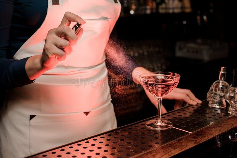 Spruzzatura femminile del barista amara sul vetro di cocktail elegante fotografia stock libera da diritti