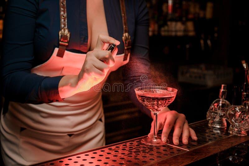 Spruzzatura femminile sexy del barista amara sul vetro di cocktail elegante fotografia stock