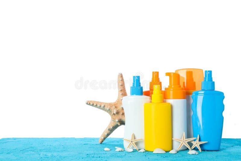 Spruzzi differenti della protezione solare con le stelle marine e conchiglie sulla tavola di colore isolata su fondo bianco fotografia stock