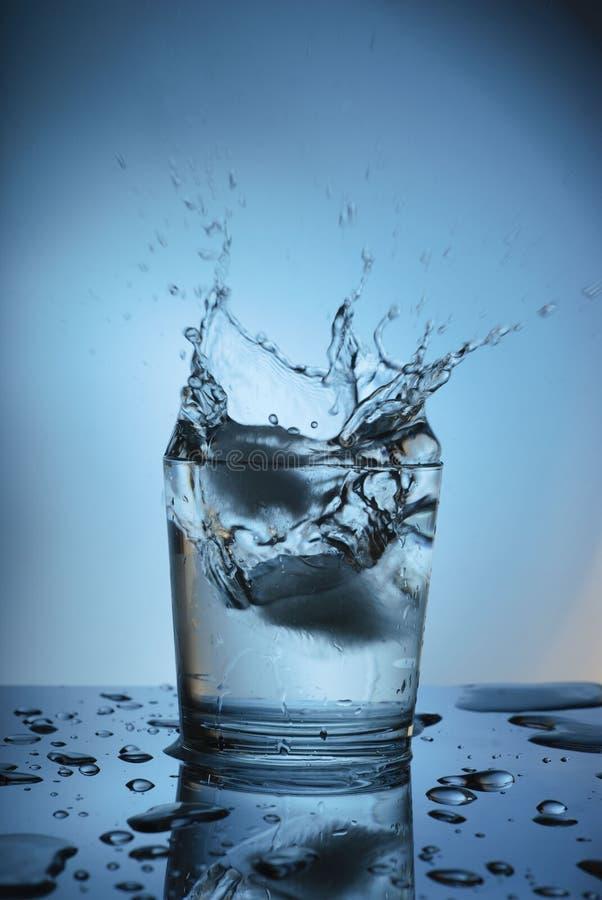 Spruzzi la chiara acqua su un fondo blu fotografie stock